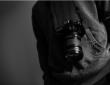 Appareil photo suspendu au cou d'une personne en sweat gris